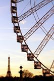 Paris Ferris wheel gondolas and Eiffel tower silhouette from place de la Concorde during twilight. Paris Ferris wheel gondolas and Eiffel tower silhouette from royalty free stock photo