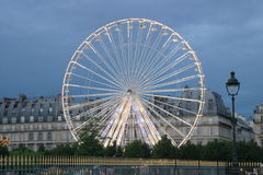 Paris ferris wheel. A large lighted ferris wheel in Paris France rises above buildings.  Picture taken at dusk to enhance the effect Royalty Free Stock Image