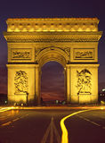 Paris floodlit Arc De Triomphe. And the Place Charles de Gaulle with traffic trails and sunset Royalty Free Stock Photography