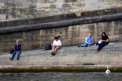PARIS, FRANÇA - 6 DE JUNHO DE 2014: Os povos não identificados descansam na terraplenagem de Seine imagem de stock