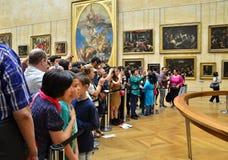 Paris, França - 13 de maio de 2015: Os visitantes tomam fotos de Mona Lisa de Leonardo da Vinci no museu do Louvre foto de stock royalty free