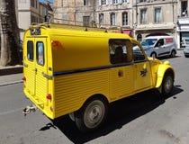 Paris, França - 29 de março de 2017: O selo de correio da entrega da camionete de entrega do carro do Citroen 2cv amarelo-coloriu fotografia de stock