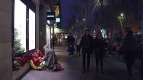 PARIS, FRANÇA - DEZEMBRO, 31, 2016 Doação local do homem atual à menina imigrante que senta-se na rua immigration imagens de stock