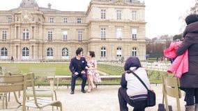 PARIS, FRANÇA - DEZEMBRO, 31, 2016 Pares asiáticos novos que levantam no parque Tiro profissional da foto da história de amor Imagens de Stock