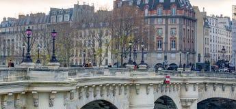 PARIS, FRANÇA - EM DEZEMBRO DE 2012: Turistas ao longo da ponte da cidade O escritório do C Foto de Stock Royalty Free