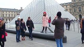 PARIS, FRANÇA - DEZEMBRO, 31, 2016 Pares que fazem fotos e selfies perto da pirâmide do Louvre Imagens de Stock