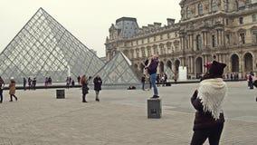 PARIS, FRANÇA - DEZEMBRO, 31, 2016 Turistas fêmeas que levantam e que fazem fotos perto do Louvre, do museu francês famoso e filme