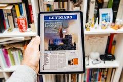 Man reading on iPad Pro about Notre-Dame de Paris fire Le Figaro