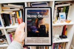 Man reading on iPad Pro about Notre-Dame de Paris fire