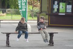 Paris, France - April 12, 2011: Boys are sitting on the bench and talking stock photography