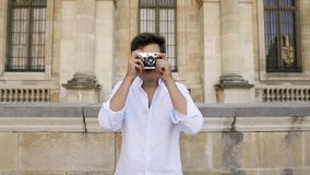 PARIS, FRANCE, APRIL 2019. Young man in white shirt making photo with a film camera on background of Louvre museum. PARIS, FRANCE, APRIL 2019. Gimbal slow motion stock footage