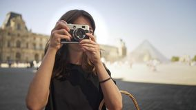 PARIS, FRANCE, APRIL 2019. Slow motion young woman making photo with a film camera on background of Louvre museum. PARIS, FRANCE, APRIL 2019. Gimbal slow motion stock video footage