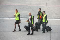Paris, France - April 2016: Group of cabin crew EasyJet walking on airfields runway at the Charles de Gaulle Airport stock photo