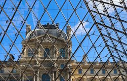 Classic details of the facade of Louvre Paris France through the glass of the pyramid stock image