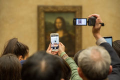 PARIS, FRANCE - APRIL 30, 2016 - Mona Lisa painting Louvre hall crowded of tourist. PARIS, FRANCE - APRIL 30, 2016 - lot of people inside louvre museum, taking Stock Images