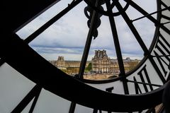 Paris / France - April 05 2019: Paris cityscape, skyline view through the famous clock in the Orsay Museum.  royalty free stock image