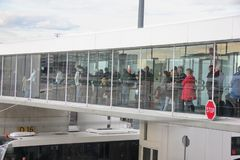 Paris, France - april 2016: People boarding an airplain using a transparent jet bridge. Side view from terminal royalty free stock photo
