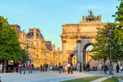 PARIS, FRANCE - APRIL 6, 2011: People walking in front of Arc de. Triomphe and Louvre Palace, sunset view Royalty Free Stock Images