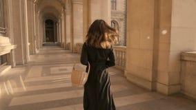 PARIS, FRANCE, APRIL 2019. Slow motion of woman in black dress running outdoors Louvre museum. PARIS, FRANCE, APRIL 2019. Slow motion of back of woman in black stock footage