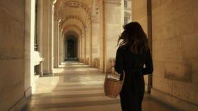 PARIS, FRANCE, APRIL 2019. Slow motion of woman in black dress walking outdoors Louvre museum. PARIS, FRANCE, APRIL 2019. Slow motion of back of woman in black stock footage