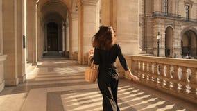 PARIS, FRANCE, APRIL 2019. Slow motion of woman in black dress running outdoors Louvre museum. PARIS, FRANCE, APRIL 2019. Slow motion of back of woman in black stock video