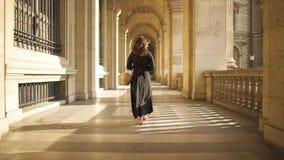 PARIS, FRANCE, APRIL 2019. Slow motion of woman in black dress walking outdoors Louvre museum. PARIS, FRANCE, APRIL 2019. Slow motion of back of woman in black stock video
