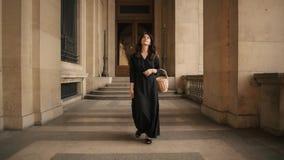 PARIS, FRANCE, APRIL 2019. Slow motion of woman in black dress walking outdoors Louvre museum. PARIS, FRANCE, APRIL 2019. Slow motion of smiling beautiful woman stock video