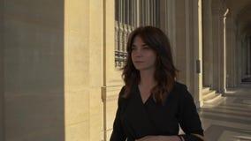PARIS, FRANCE, APRIL 2019. Slow motion of woman in black dress walking outdoors Louvre museum. PARIS, FRANCE, APRIL 2019. Slow motion of woman in black dress stock video footage