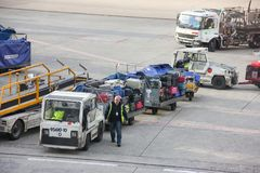 Paris, France - april 2016: Worker stacking luggage on trailer from conveyor on runway going to transportation car. Charles de Gaulle Airport royalty free stock photos