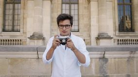 PARIS, FRANCE, APRIL 2019. Young man in white shirt making photo with a film camera on background of Louvre museum. PARIS, FRANCE, APRIL 2019. Gimbal slow motion stock video