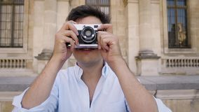 PARIS, FRANCE, APRIL 2019. Young man in white shirt making photo with a film camera on background of Louvre museum. PARIS, FRANCE, APRIL 2019. Gimbal slow motion stock video footage