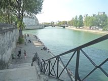 Paris, France, August 18 2018: people sitting and walking along the river side stock photos