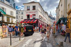 Street scene with traditional cafes and art galleries in Montmartre, Paris. PARIS,FRANCE -AUGUST 4,2017 : Street scene with traditional cafes and art galleries Royalty Free Stock Image