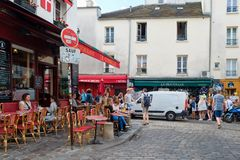 Street scene with traditional outdoor cafes in Montmartre, Paris. PARIS,FRANCE -AUGUST 4,2017 : Street scene with traditional outdoor cafes in Montmartre Royalty Free Stock Images