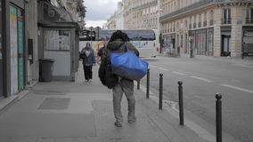 PARIS, FRANCE- August 2018: unrecognized homeless beggar walks down the street in the center of Paris. Against the. Background of a typical french cityscape stock video footage