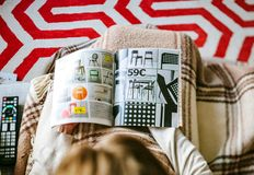 Reading IKEA Catalogue woman read from above search chair Stock Photos