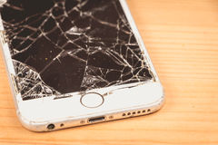 Broken iPhone 6S developed by the company Apple Inc. Paris, FRANCE - August 26, 2017: on a wooden background, a white iPhone 6S developed by the company Apple stock photos