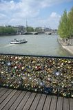 Paris, France: Bridge of arts with love locks, a boat on the seine, eiffel tower royalty free stock photo