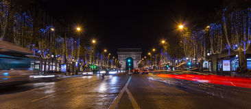 Paris,France: Champs Elysees and Triumphal Arch illuminated for Christmas. Paris,France: Champs Elysees and Triumphal Arch with traffic cars in the dusk Royalty Free Stock Photos
