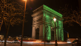 Paris,France: Champs Elysees and Triumphal Arch illuminated in green. Paris,France: Champs Elysees and Triumphal Arch with traffic cars in the dusk,illuminated Royalty Free Stock Image