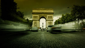 Paris,France: Champs Elysees and Triumphal Arch with traffic cars. In the dusk Royalty Free Stock Images