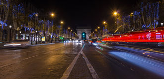 Paris,France: Champs Elysees and Triumphal Arch illuminated for Christmas. Paris,France: Champs Elysees and Triumphal Arch with traffic cars in the dusk royalty free stock photo