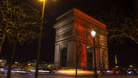 Paris,France: Champs Elysees and Triumphal Arch illuminated in red. Paris,France: Champs Elysees and Triumphal Arch with traffic cars in the dusk,illuminated in royalty free stock photo