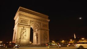 Paris, France - Circa August 2017: Illuminated at night Arch of Triumph in Paris, Champs Elysees. Cars and buses passing by stock footage