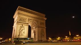 Paris, France- Circa August 2017: Illuminated at night Arch of Triumph in Paris, Champs Elysees. Cars and buses passing by stock footage