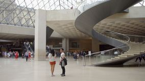 PARIS, FRANCE- CIRCA August 2017: Louvre museum. Inside view of famous Louvre pyramid, people walking by. PARIS, FRANCE- CIRCA August 2017: Louvre museum. Inside stock footage