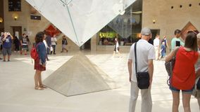 PARIS, FRANCE- CIRCA August 2017: Louvre museum. Inside view of famous Louvre pyramid, people walking by. PARIS, FRANCE- CIRCA August 2017: Louvre museum. Inside stock video