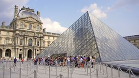 PARIS, FRANCE- CIRCA August 2017: Louvre museum. View of famous Louvre pyramid from outside, people walking by. Line to museum entrance stock video footage