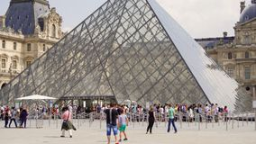 PARIS, FRANCE- CIRCA August 2017: Louvre museum. View of famous Louvre pyramid from outside, people walking by. Line to museum entrance stock video