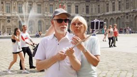 PARIS, FRANCE- CIRCA August 2017: Senior couple making selfie with smartphone on vacation in Paris. Having silly fun, happy traveling together stock video